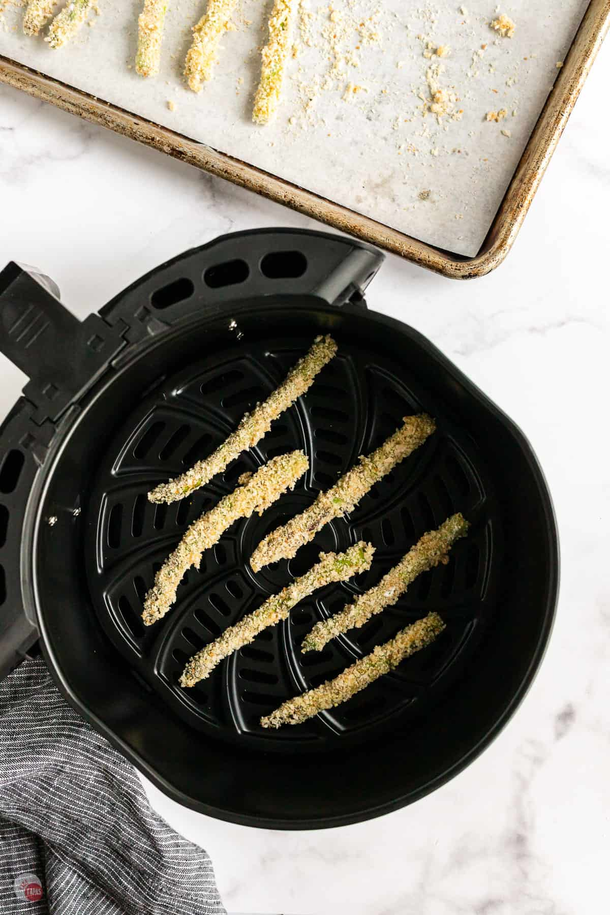 unbaked asparagus in an air fryer basket
