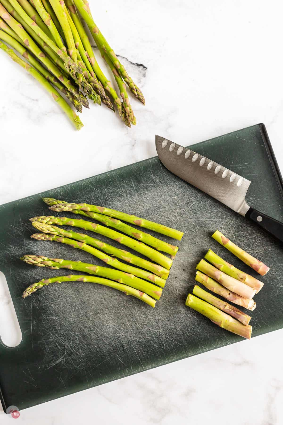 asparagus being cut on a board