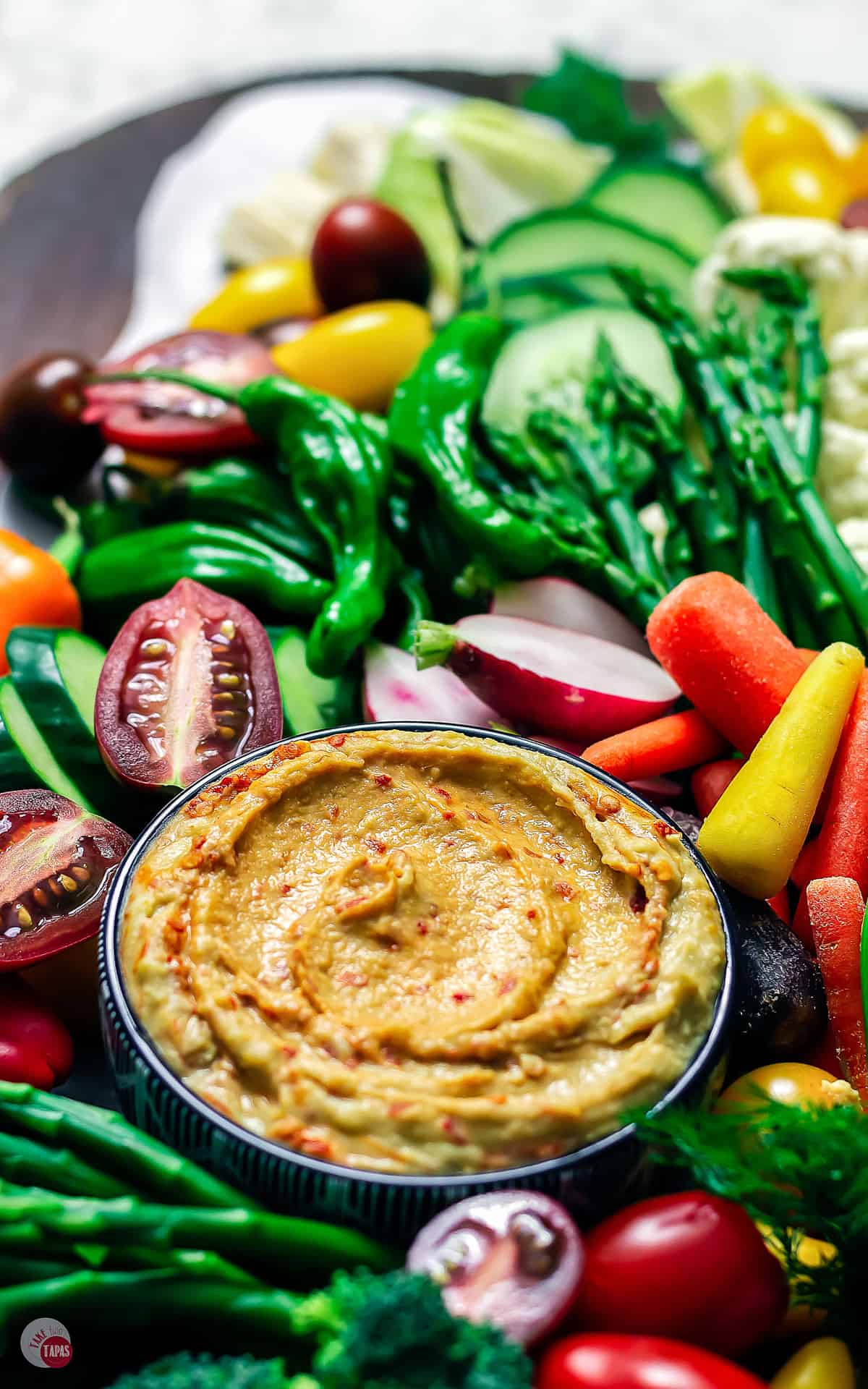 close up of hummus in a bowl on crudite platter