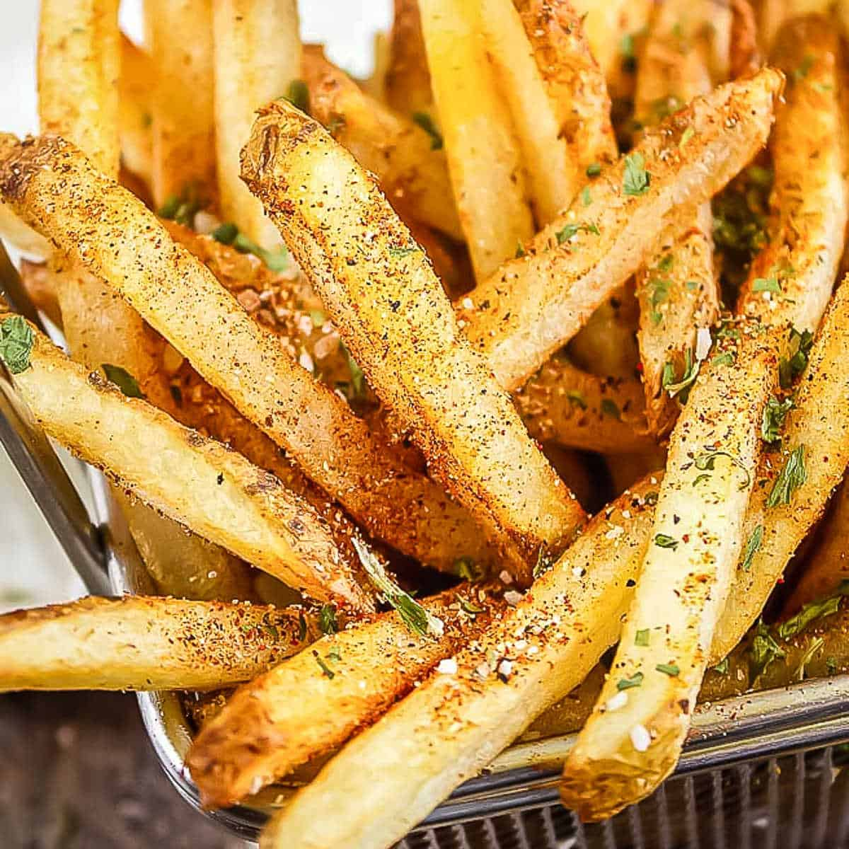 wire basket of french fries with seasoning with a napkin in the back