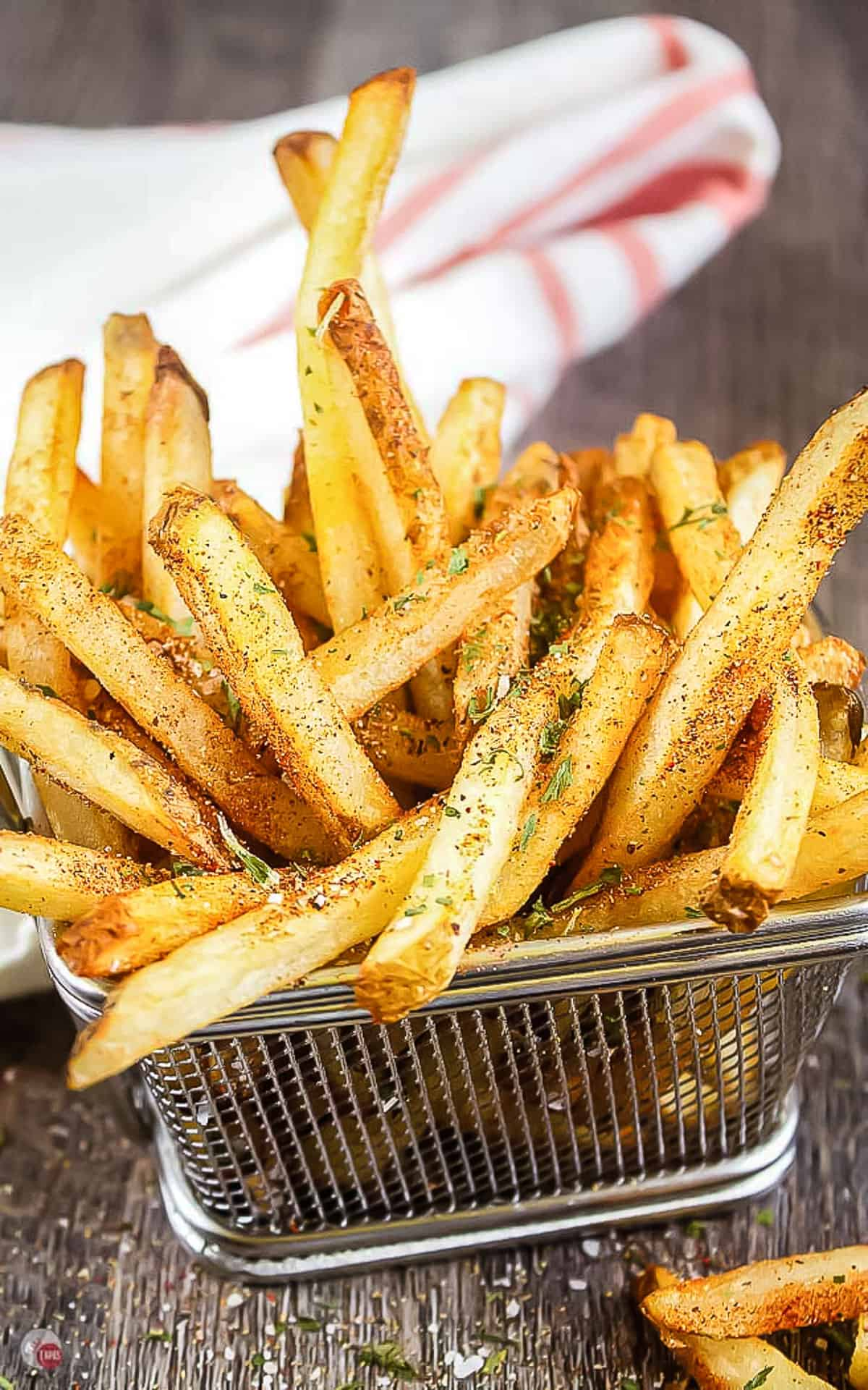 wire basket of fries with seasoning on them and a white napkin in the back