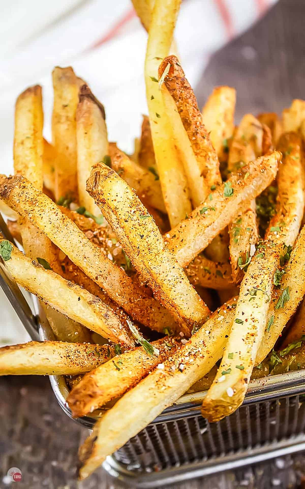 wire basket of fries with seasoning on them