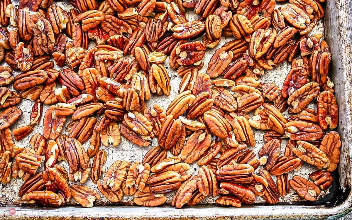 close up of toasted pecans on a baking sheet